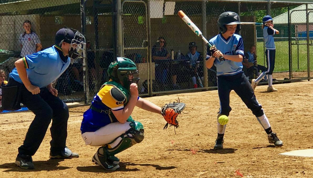 PROUD MOMENT: Alex Maiden bats for NSW at the national softball championships in Canberra with older brother Todd (left) officiating as umpire.