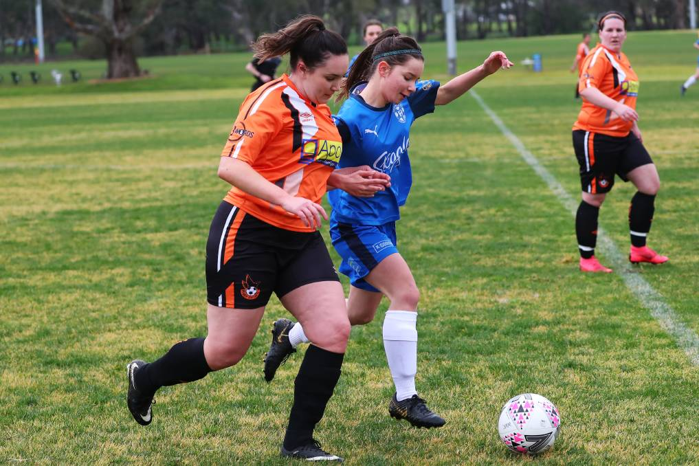 SHOULDER TO SHOULDER: Hanwood's Jemimah Brooker and Wagga United's Bronte Langbroek battle for possession during Hanwood's convicing win. PHOTO: Emma Hillier